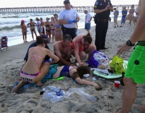 Emergency responders assist a teenage girl at the scene of a shark attack in Oak Island, N.C., Sunday, June 14