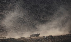 Dust rises as a tractor passes after dumping garbage at a waste yard on the outskirts of New Delhi, India, Tuesday, June 16, 2015. Never mind lowering the rate of death from air pollution in India and China. Just keeping those rates steady will demand urgent action to clear the skies, according to a new report published Tuesday.  (AP Photo/Altaf Qadri)