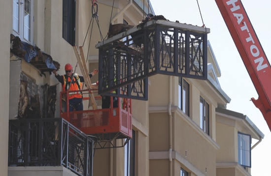 Workers remove part of a fourth floor balcony that fell onto the balcony below at the Library Gardens apartment complex in Berkeley, Calif.