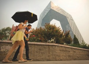 CORRECTS SOURCE OF STUDY A woman wearing a face mask and carrying an umbrella walks past the China Central Television (CCTV) headquarters building on a smoggy day in Beijing, Tuesday, June 16, 2015. A study published in the journal, Environmental Science & Technology, shows that India and China would need to reduce average levels of tiny, inhalable particulate matter called PM 2.5 by 20 to 30 percent merely to offset their demographic changes and keep mortality rates steady. That still won't get them to the WHO's recommendation of 10 micrograms per cubic meter, but it could help avoid several hundred thousand premature deaths every year. (AP Photo/Mark Schiefelbein)