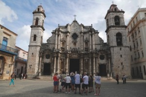 A group of American tourists on a guided tour listen to a information on the Cathedral, in Old Havana