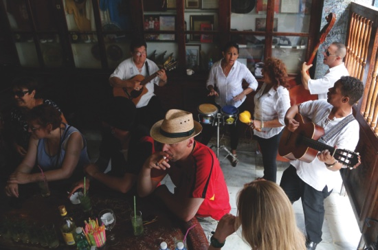 Tourists enjoy cigars, mojitos and live music at the Bodeguita del Medio Bar, frequented by the late American novelist Ernest Hemingway in Old Havana, Cuba