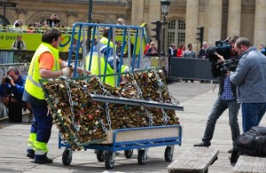 A Paris city employee removes a railing loaded with locks on the famed Pont des Arts bridge in Paris, Monday June 1, 2015. Lovers in Paris, beware: City authorities are taking down thousands of padlocks affixed to the famed Pont des Arts bridge. The city council says the locks, usually hung by couples to express eternal love, cause long-term damage to Paris heritage and sometimes pose a security risk. Last summer a chunk of fencing fell off under their weight. (AP Photo/Remy de la Mauviniere)
