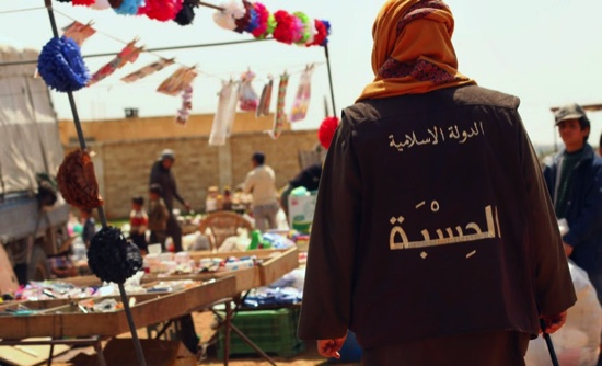 """In this photo released on April 17 by a militant website, a member of the Islamic State group'svice police known as """"Hisba,"""" patrols a market in Raqqa City, Syria"""