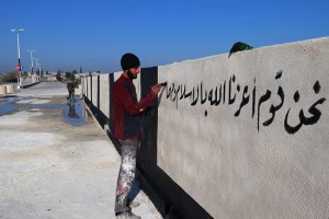 """A member of the Islamic State group writes in Arabic, """"we are a people whom God has honored with Islam,"""" on a newly painted wall"""