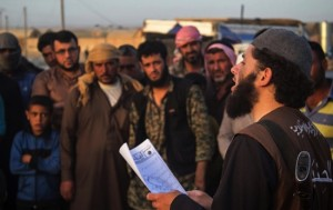 """A member of the Islamic State group's vice police known as """"Hisba,"""" right, reads a verdict handed down by an Islamic court sentencing many they accused of adultery to lashing"""