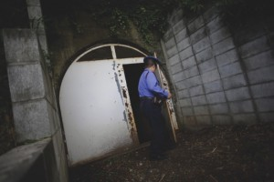 A security guard closes a metal door of an entrance to the tunnels