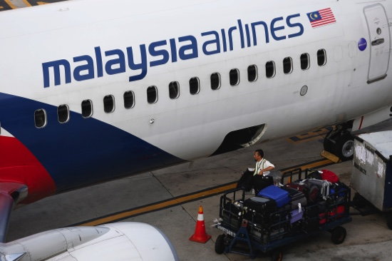A Malaysia Airlines ground staff member unloads luggage from a plane at Kuala Lumpur International Airport in Sepang, Malaysia