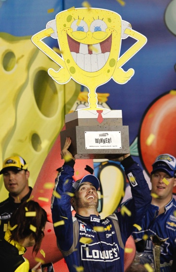 NASCAR driver Jimmie Johnson (48) holds the trophy for winning the SpongeBob SquarePants 400 Sprint Cup Series auto race at Kansas Speedway in Kansas City, Kan.