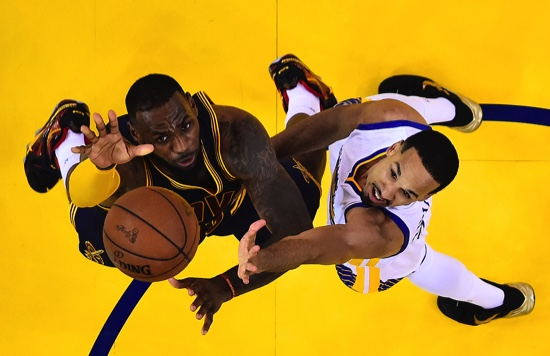 Cleveland Cavaliers forward LeBron James, left, reaches for the ball next to Golden State Warriors guard Shaun Livingston during the second half of Game 5 of basketball's NBA Finals in Oakland, U.S.