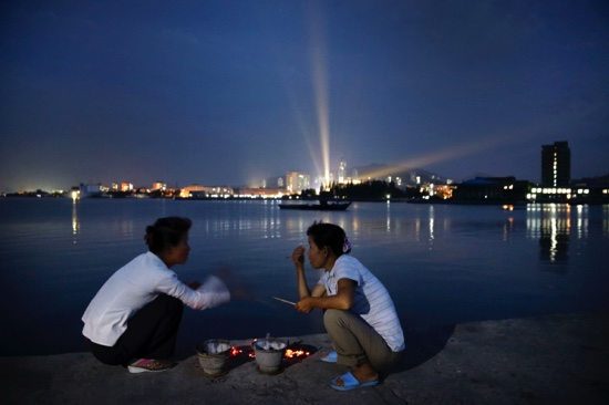 North Korean women talk over pots of burning charcoal for cooking seafood on a pier leading to Jangdok Island at dusk, in Wonsan, North Korea
