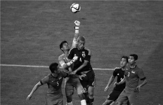 Japan's Keisuke Honda, center right, and Singapore's goalkeeper Mohamad Izwan Bin Mahbud, center left, vie for the ball during their second round soccer match of regional qualifiers for the 2018 World Cup, in Saitama, north of Tokyo