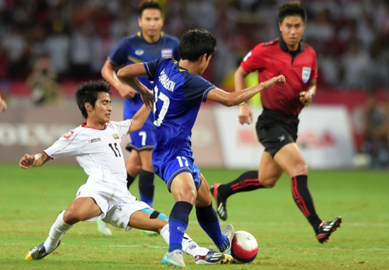 Hein Thiha Zaw of Myanmar, left, is tackled by Tanaboon Kesarat of Thailand, centre, during the soccer final at the SEA Games in Singapore
