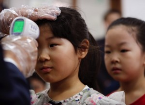 A student has her temperature checked as a precaution against MERS at Gwanghui Elementary School in Seoul