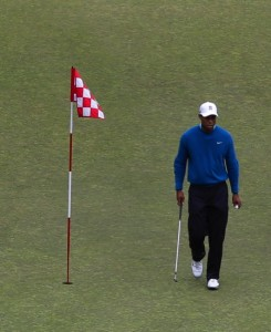 Tiger Woods walks past the flag as he practices