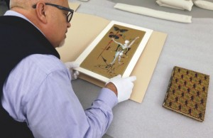 Michael Labrie, director of collections and exhibitions at the Walt Disney Family Museum, looks at art work by Salvador Dali that was put on the cover of the 1961 Bal Chouinard program, in a collections room at the Disney museum in San Francisco