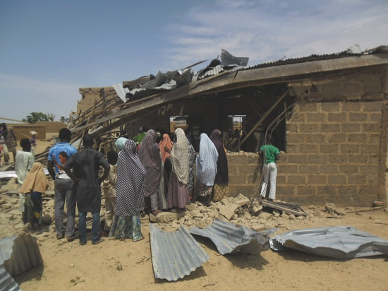 People gather at the site of suicide bomb attack at Redeem Christian church in Potiskum