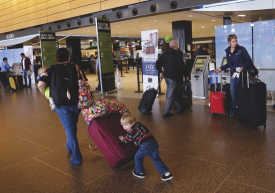 In this March 24,  photo, Colin Drummond, 4, pushes luggage from behind as he walks with family members to check-in a relative for an Alaska Airlines flight at Seattle-Tacoma International Airport in SeaTac, Wash.