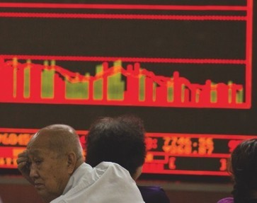 Investors monitor stock prices at a brokerage in Beijing