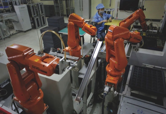 A Chinese worker is seated next to orange robot arms at Rapoo Technology factory in southern Chinese industrial boomtown of Shenzhen