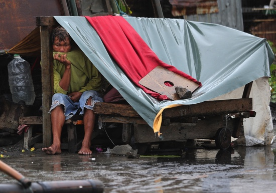 A Filipino man sits inside his makeshift home as strong winds and rains caused by Typhoon Koppu hits the coastal town of Navotas, north of Manila