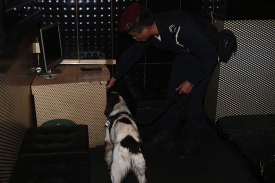 A police officer inspects a local karaoke parlor where drugs where hidden