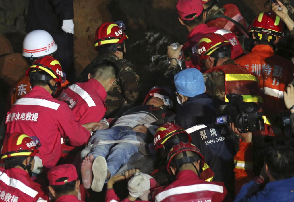 In this photo provided by China's Xinhua News Agency, a survivor is rescued at the site of landslide at an industrial park in Shenzhen, south China's Guangdong Province, early Wednesday, Dec. 23, 2015. Rescuers have pulled a man out alive after he was buried for more than 60 hours in a massive landslide in southern China. (Yin Gang/Xinhua News Agency via AP) NO SALES