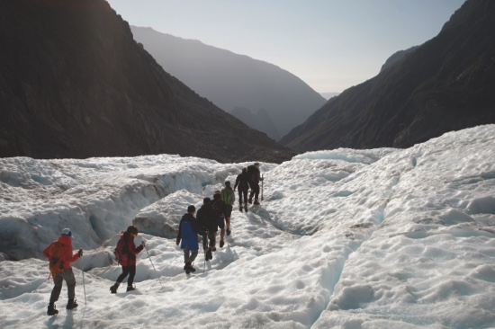 Tourists who have taken a helicopter trip onto the Fox Glacier follow a guide