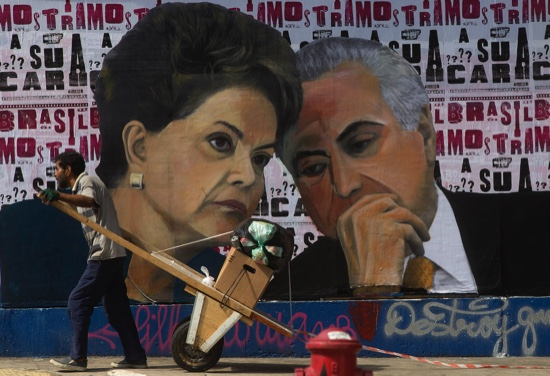 A man pushes a cart loaded with garbage for recycling in front of a mural depicting Brazil's President Dilma Rousseff and Vice President Michel Temer