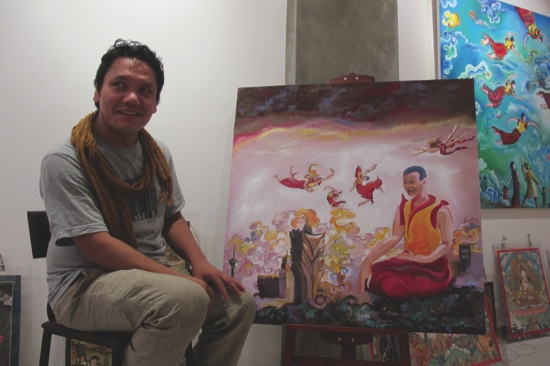 Tashi Norbu sits next to a painting made specifically for the exhibition