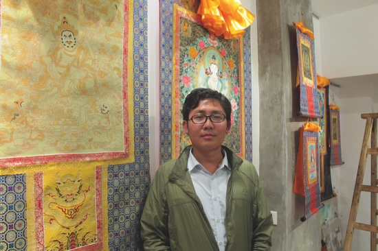 Li Ben Ta Shi stands in front of a traditional Thangka