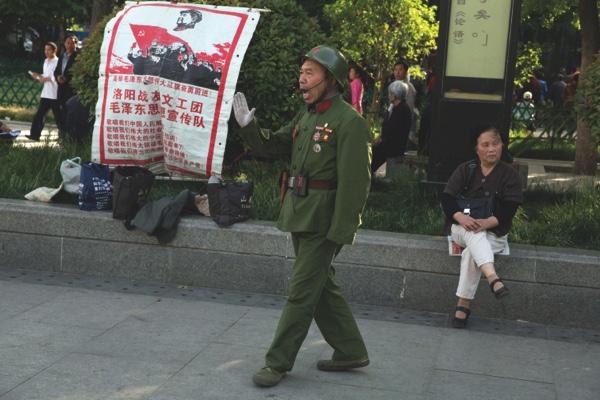 Zhao Shunli sings near a banner promoting Mao Zedongs ideology on Zhouwangcheng plaza in Luoyang in central China's Henan province