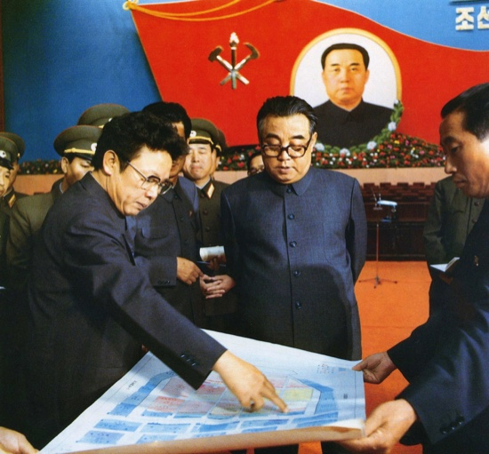 In this October 1980 photo provided by the Korea News Service (KNS), then North Korean leader Kim Il Sung (center), and his son Kim Jong Il (left), talk about the preparation for the convention of North Korea's Workers' Party in Pyongyang