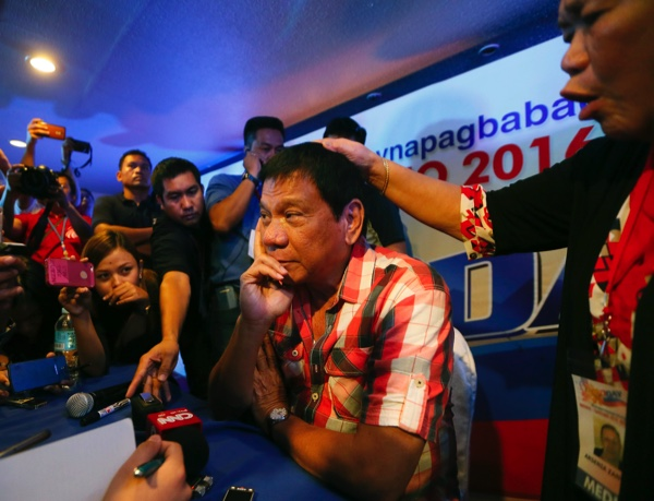 Front-running presidential candidate Mayor Rodrigo Duterte is prayed over by a supporter during a news conference shortly after voting in a polling precinct at Daniel R. Aguinaldo National High School, Matina district, his hometown in Davao city