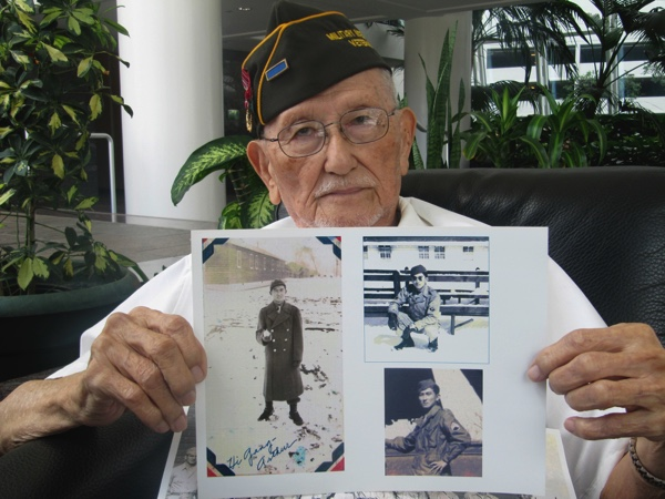 Arthur Ishimoto, 93, a Japanese-American and U.S. Army Military Intelligence Service veteran, poses with archival photographs of himself as he is interviewed in Honolulu