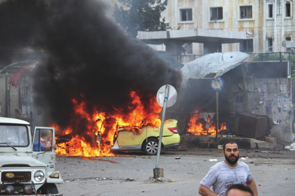 In this photo released by the Syrian official news agency, people gather in front of a burning car at the scene where suicide bombers blew themselves up yesterday in the coastal town of Tartus
