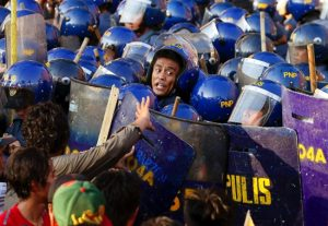 A police officer yells at his colleagues during a clash with protesters in Manila to mark the International Labor Day
