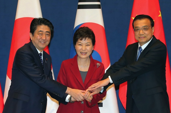 South Korean President Park Geun-hye (center), poses with Japanese Prime Minister Shinzo Abe (left), and Chinese Premier Li Keqiang as they meet to hold a trilateral summit at the presidential house in Seoul