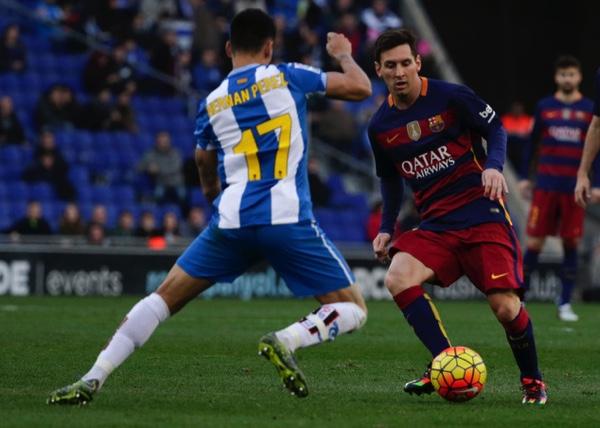 Barcelona's Lionel Messi (right), fights for the ball against Espanyol's Hernan Perez during a Spanish La Liga soccer match at Cornella-El Prat stadium in Cornella Llobregat