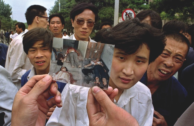 In this file photo take June 5, 1989, people on Chang'an Boulevard hold up a photo that they described as dead victims of the violence against pro-democracy protesters on Tiananmen Square, Beijing