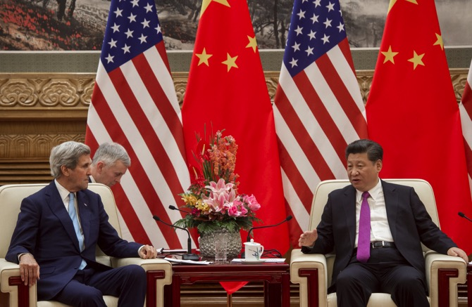 Chinese President Xi Jingping (right) talks to U.S. Secretary of State John Kerry (left) during a meeting at the Great Hall of the People in Beijing
