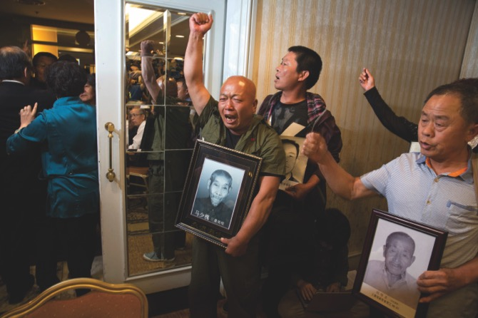 Ma Wenyi (left) holding a photo of his father who was forced to work during World War II at a mine for Mitsubishi Mining Corp., shouts as he demands to join a press conference in Beijing