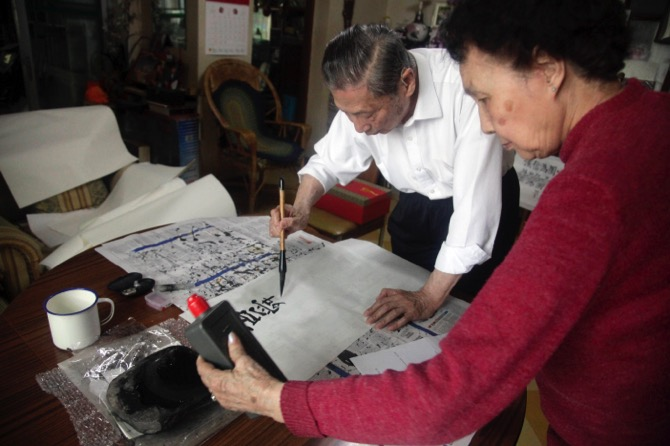 Mao Yushi writes calligraphy as his wife Zhao Yanling prepares the ink at their home in Beijing. Targeted by radical Red Guards during China's tumultuous Cultural Revolution, Mao Yushi saw his family home ransacked, underwent hard labor and was lashed bloody with copper wires along with his father