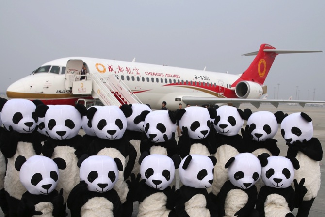 People in panda costumes pose in front of a Chengdu Airlines ARJ21-700 plane before its first commercial flight at Chengdu Shuangliu International Airport