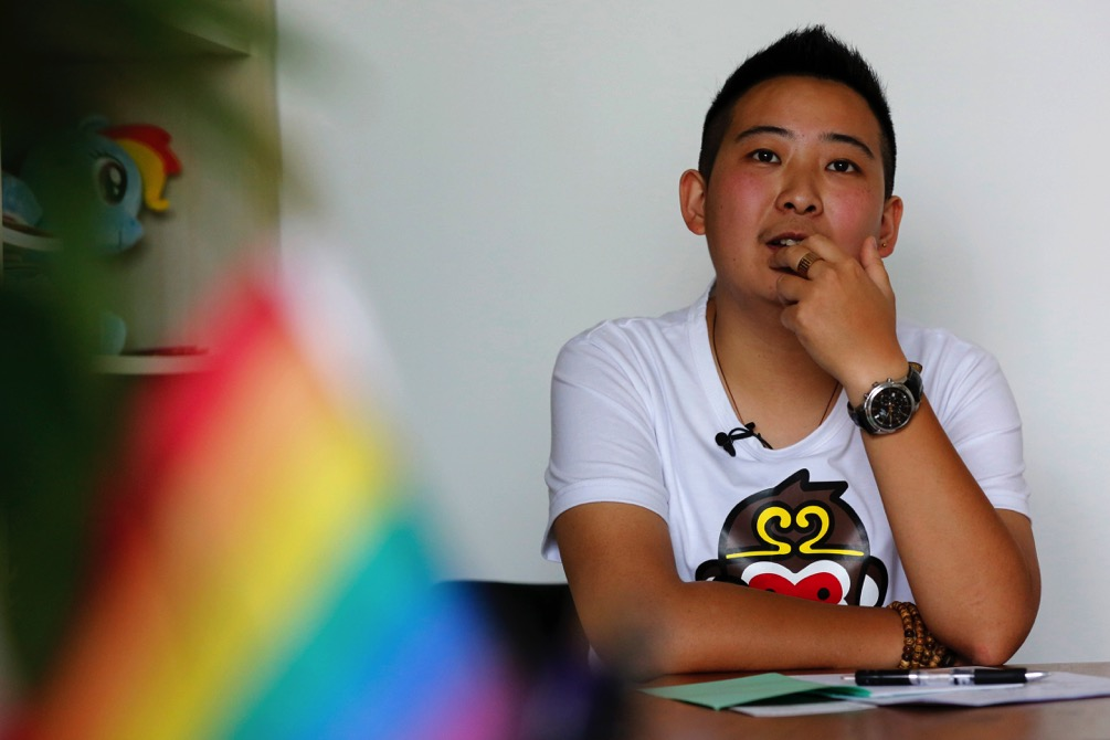 """A transgender equal rights supporter who goes by the name of """"Mr. C"""" pauses during an interview with AP in Beijing"""
