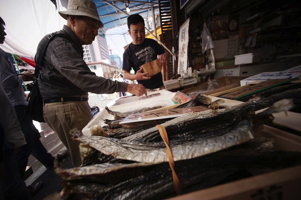 A man buys dried fish from a shop in Tokyo on May 18. Japan's economy grew at a better than expected 1.7 percent annual pace in the first quarter of 2016