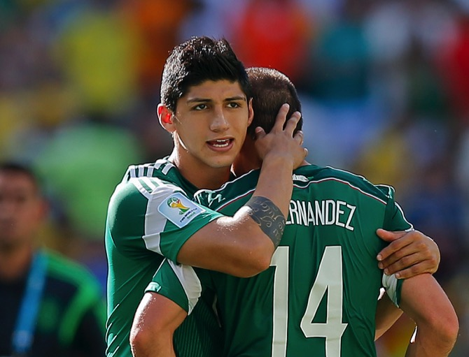 Mexico's Alan Pulido consoles teammate Javier Hernandez (14) after the Netherlands defeated Mexico 2-1 during the World Cup round of 16 soccer match