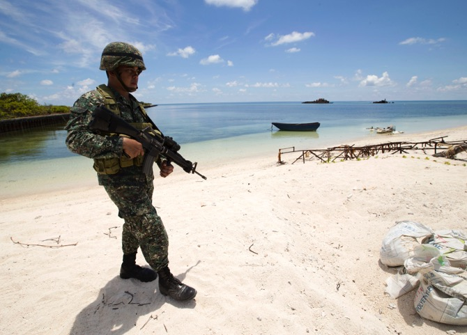 A Filipino soldier patrols at the shoar of Pagasa island (Thitu Island) in the Spratly group of islands in the South China Sea