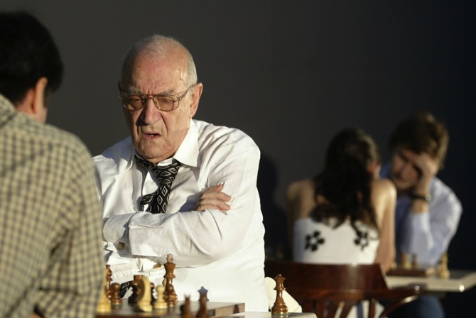 In this Oct. 22, 2006 file photo, chess master Victor Korchnoi (center) plays against Gilberto Hernandez of Mexico as Alexandra Kosteniuk, of Russia during the Mexico City Chess Festival