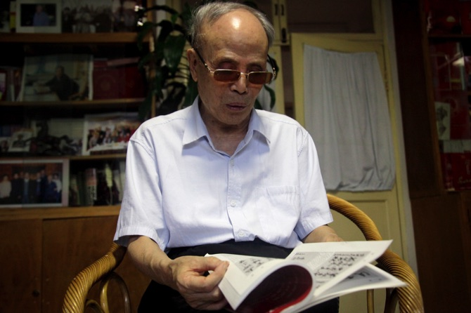 Du Daozheng browses his Yanhuang Chunqiu magazine during an interview at his home in Beijing